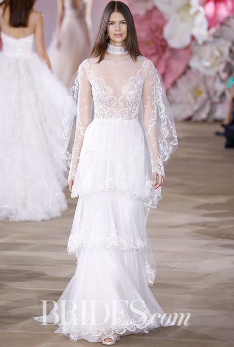 """Brides.com: . """"Pure"""" A-line wedding dress with illusion V-neck bodice, sheer sleeves, and scalloped embroidered tiered skirt, Ines Di Santo"""